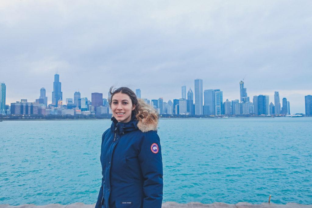 woman stands near Planetarium in Chicago, skyline behind her