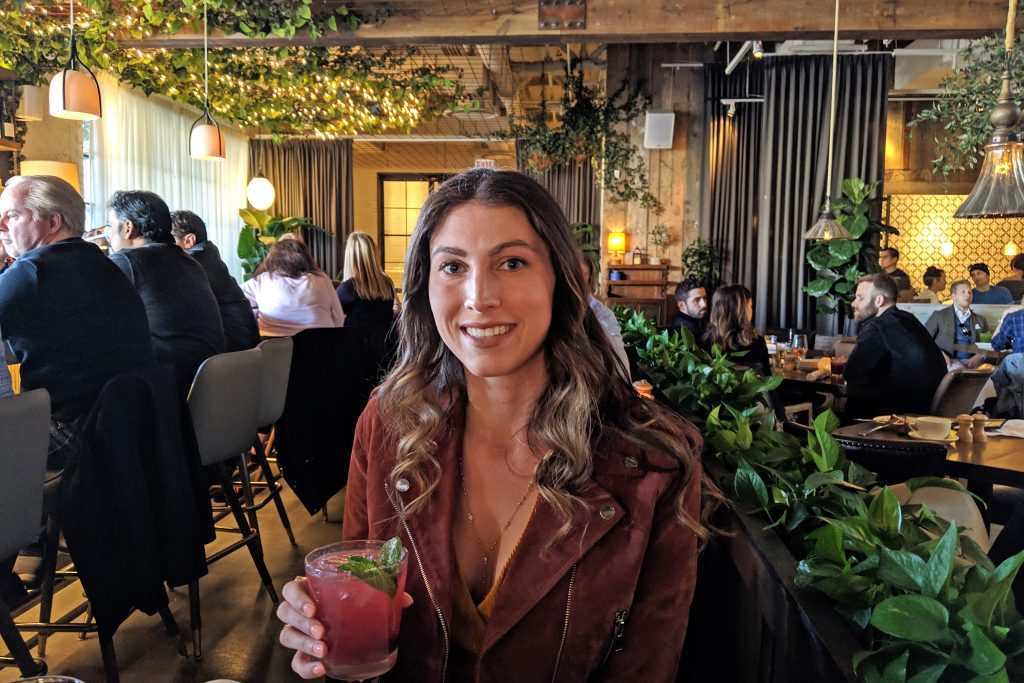 Girl holding drink at Aba restaurant in Chicago