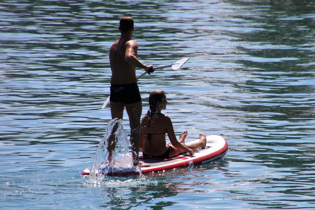 couple on one stand-up paddle board