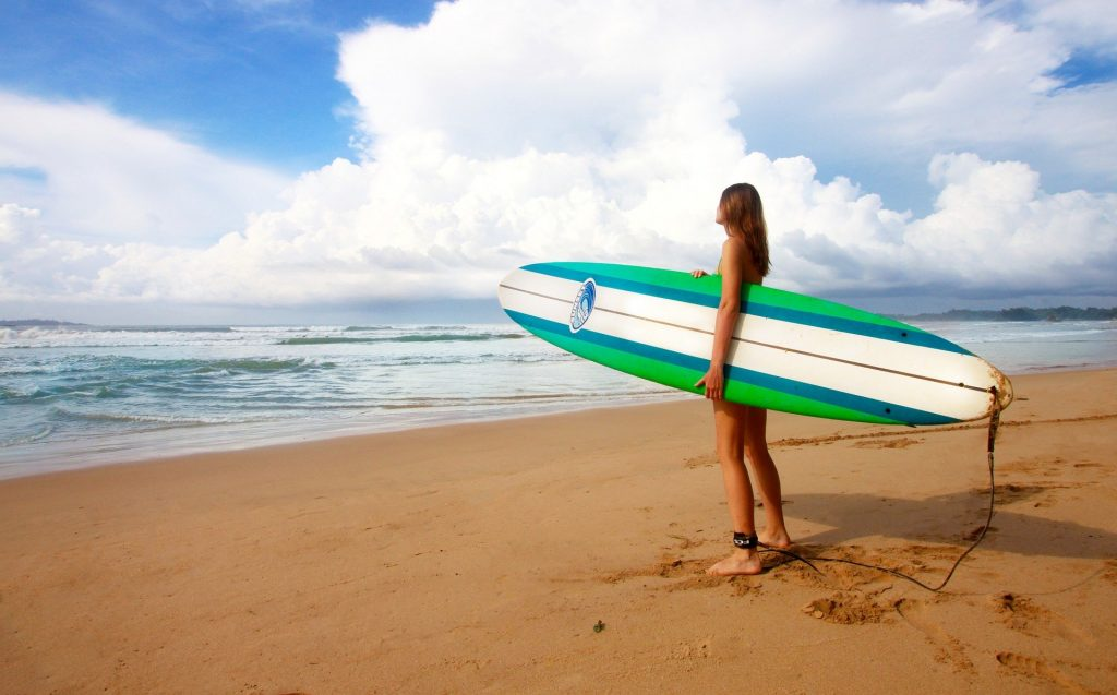 girl with surf board in front of ocean
