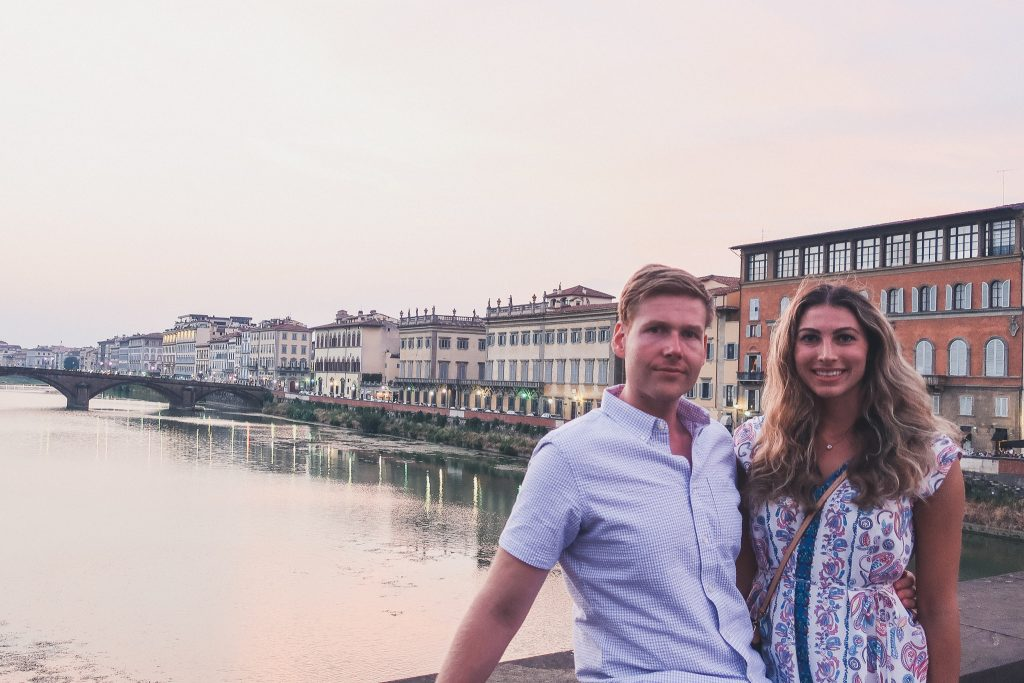 couple on a bridge, you can see the Ponte Santa Trinita behind them