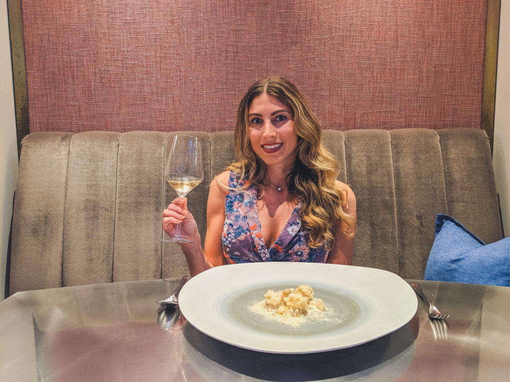 woman raises a glass at Chicago's alinea restaurant