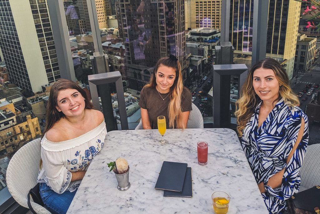 3 girls sit with drinks surrounded by Chicago skyscrapers