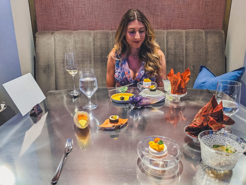 woman looks out on to food served at Alinea