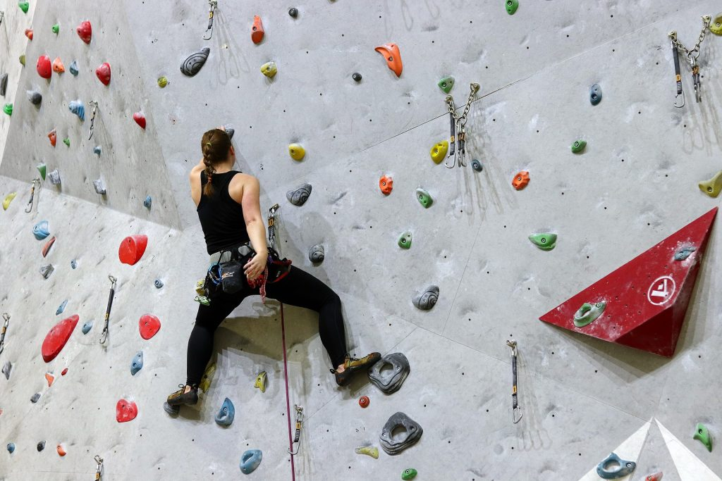 man on rock climbing wall, holding on with 1 hand