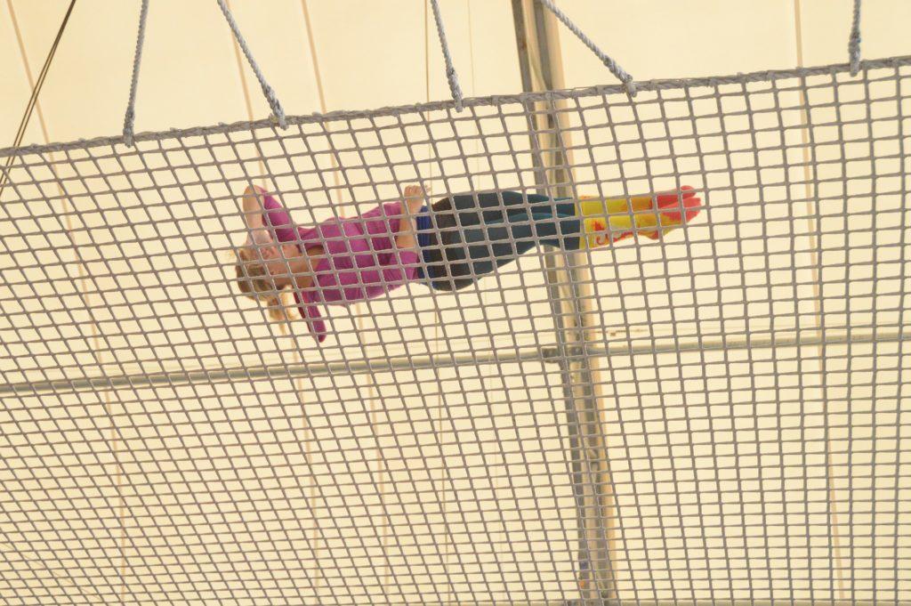 woman doing trapeze, gracefully falling onto trampoline