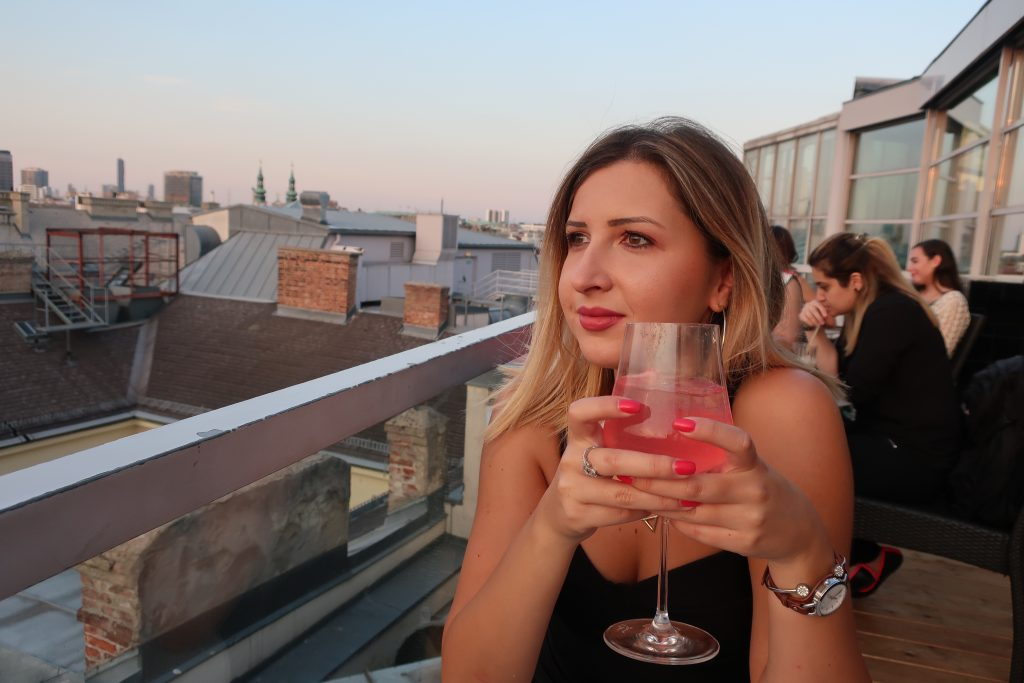 woman sips cocktail at Sky Bar in Vienna