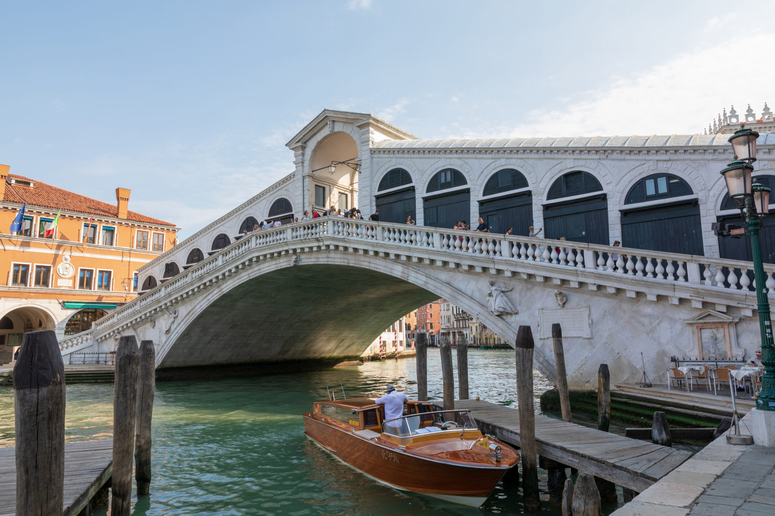 Venice, Italy - July 1, 2018: Panoramic view of Rialto Bridge (Ponte di Rialto) is the oldest of the four bridges spanning the Grand Canal in Venice. Landscape of summer sunny day and blue sky