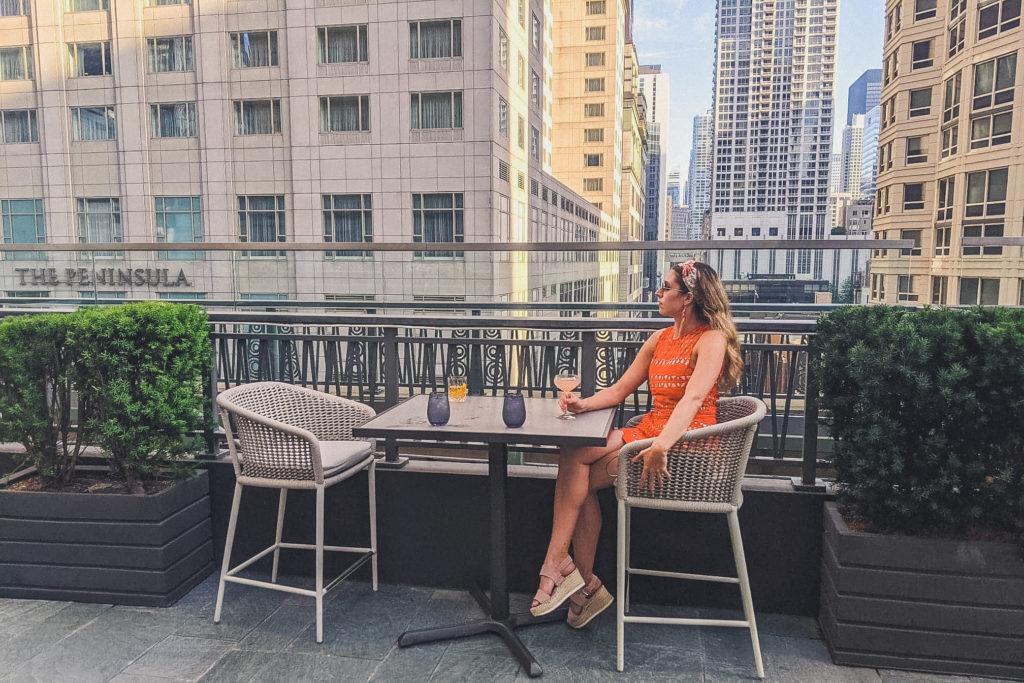 woman sips drink at NoMi Garden in Chicago