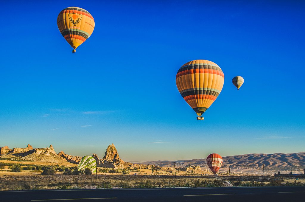 3 hot air baloons in the sky above the Nevada desert