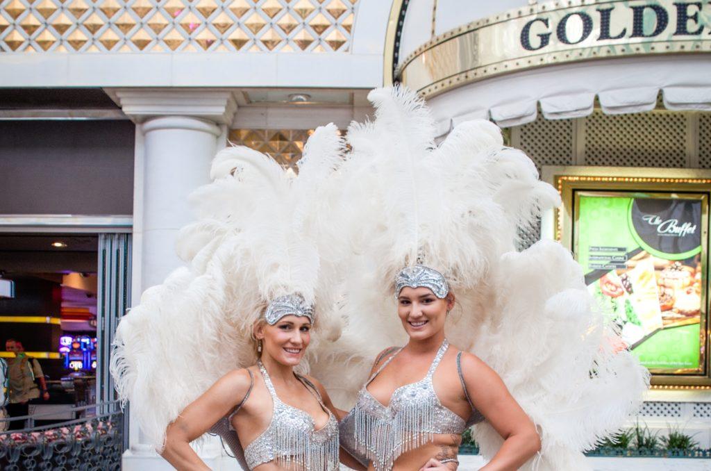 Vegas showgirls wearing white feathers