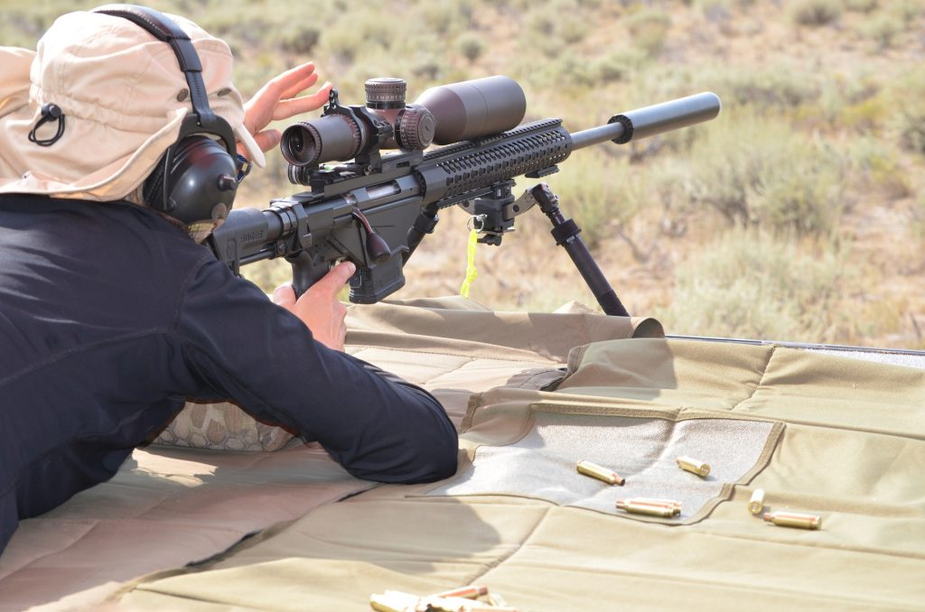man takes aim at outdoor shooting range with sniper