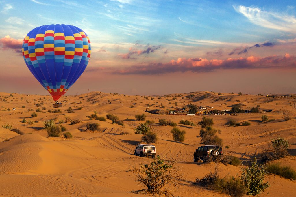 Hot air balloons landing sky in a desert sand dune is a popular activity rally off-road car among tourists in Dubai.