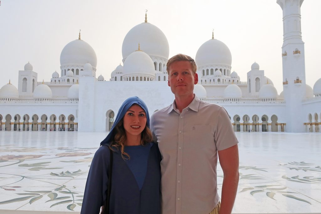 couple in front of the grand mosque in Abu Dhabi