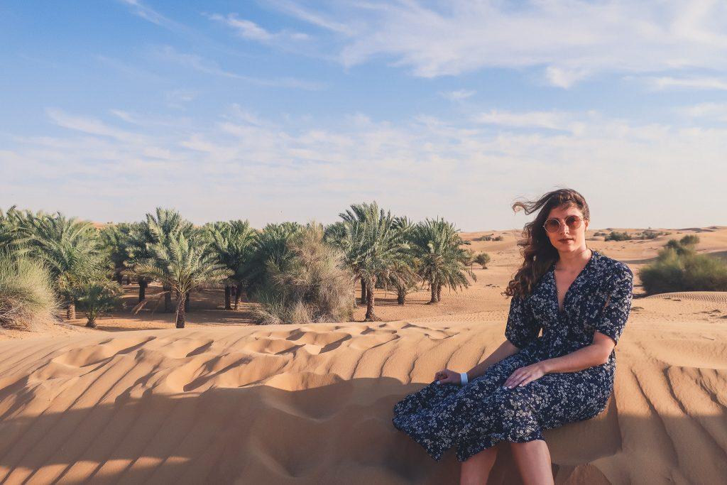 girl sits in the Arabian desert near dubai, palm trees are seen among dunes