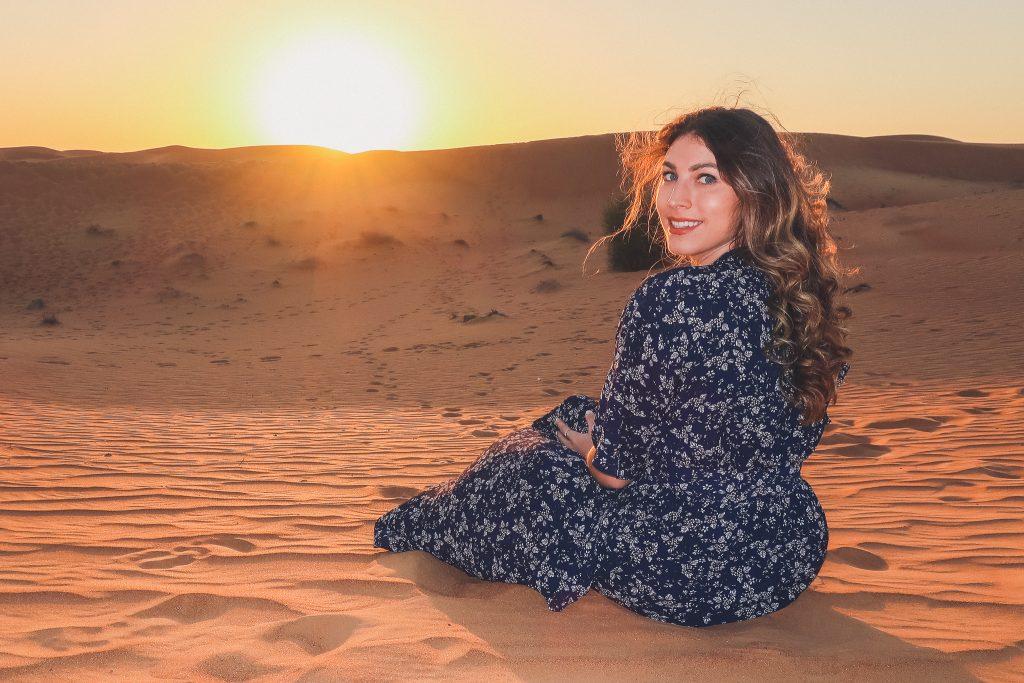 sunset at the arabian desert near dubai, girl looks towards camera