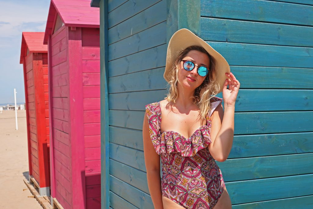 Girl at Playa de la Patacona in front of colorful dressing rooms