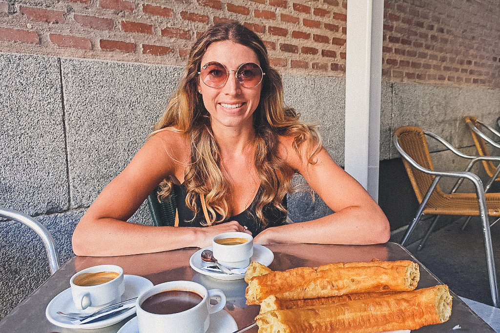 woman happily sits with churros in Madrid