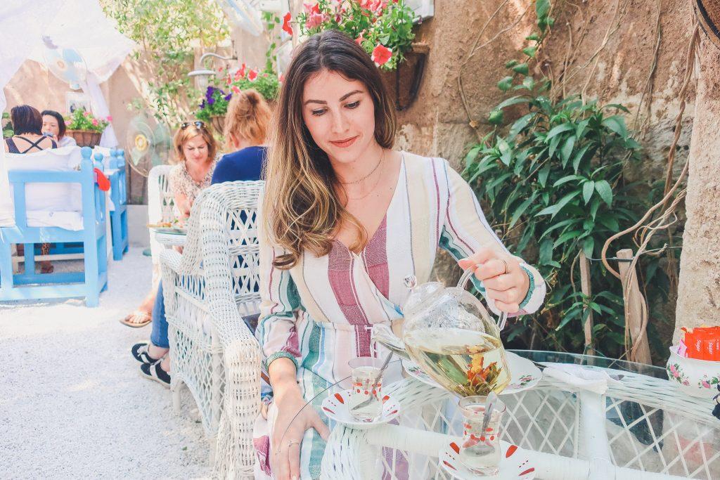 girl pours tea at the Arabian Teahouse in Dubai