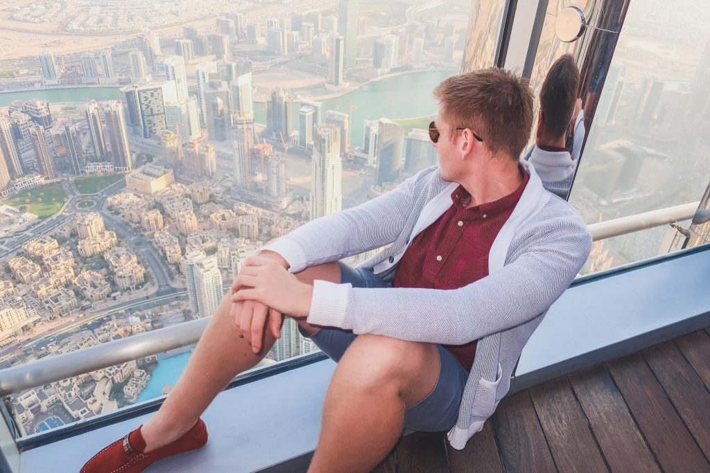 man sits and looks out at the view from the 148th floor of the Burj Khalifa