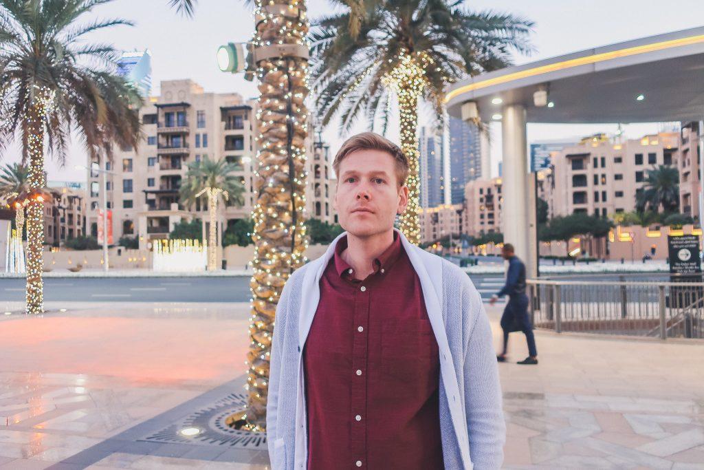 man at Burj Park in Dubai around sunset