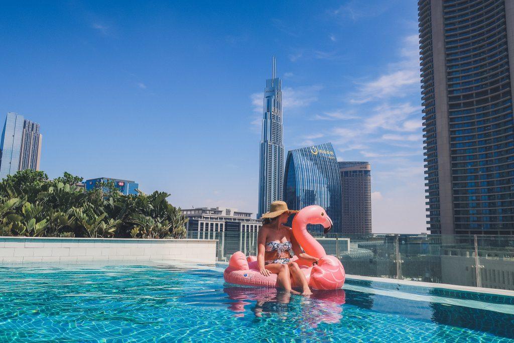 girl in Sofitel Downtown Dubai's pool, sitting on inflatable flamingo pool toy