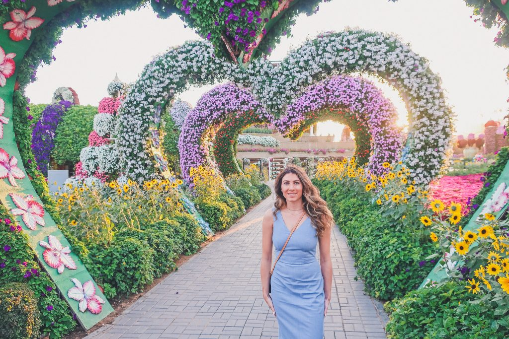girl stands between giant flower hearts and the dubai miracle garden