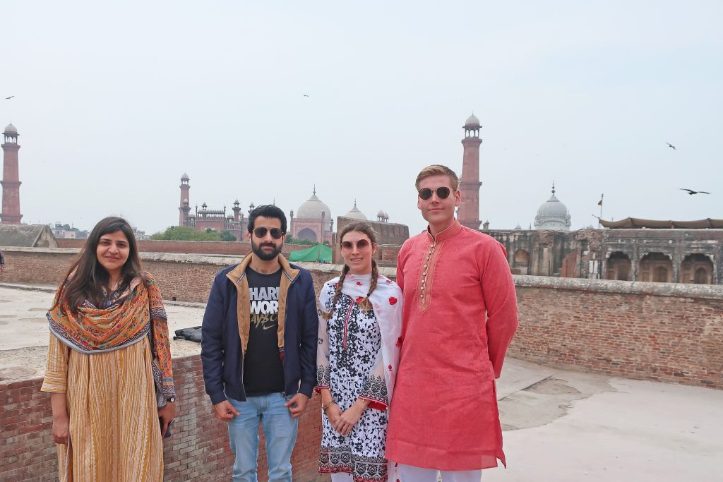 Mosque seen from inside the lahore fort, 4 friends stand in front of it