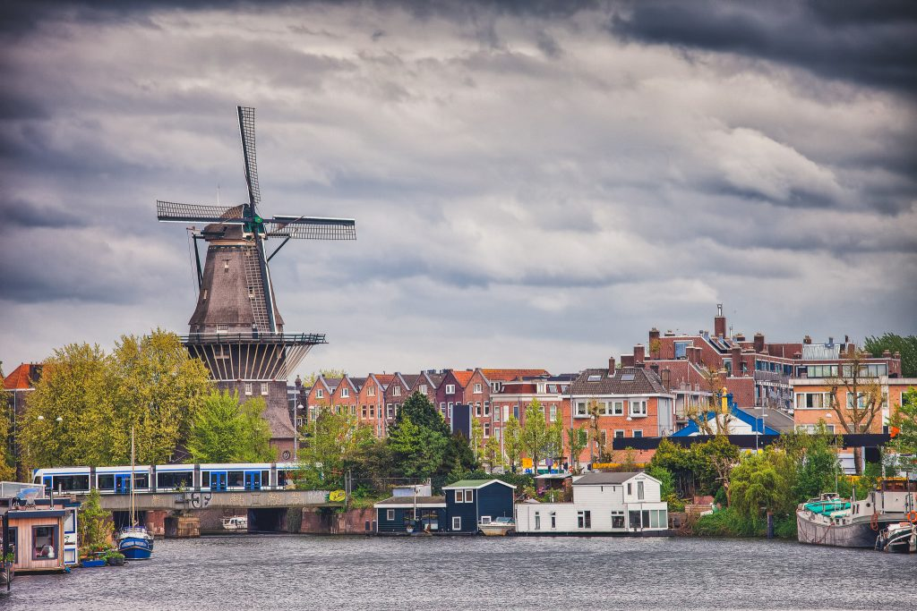 The Gooyer Windmill and houses by the canal, city of Amsterdam, North Holland, the Netherlands.