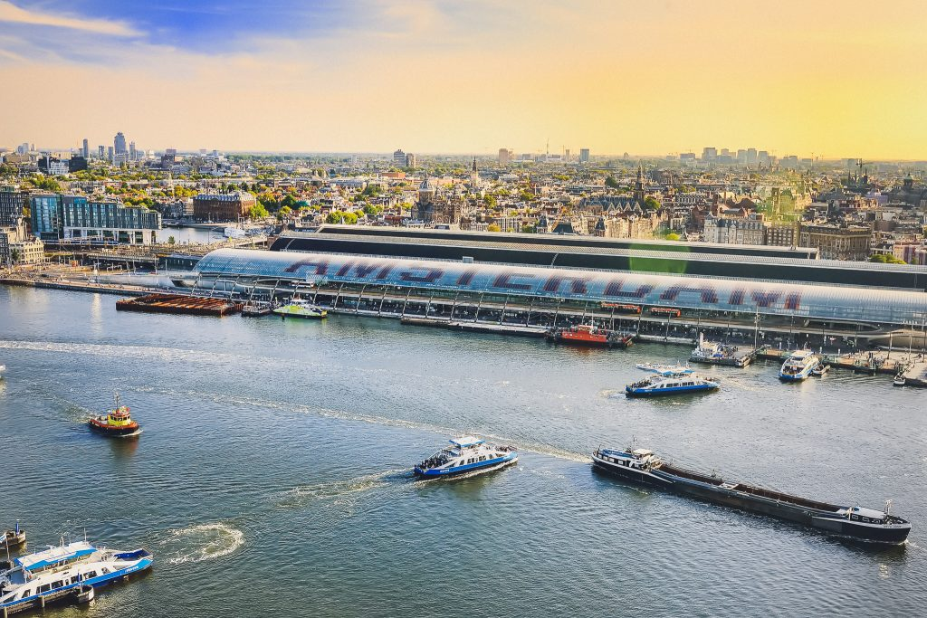 Amsterdam cityscape top view at sunset. River with ships, boats, Central station. From A'Dam lookout