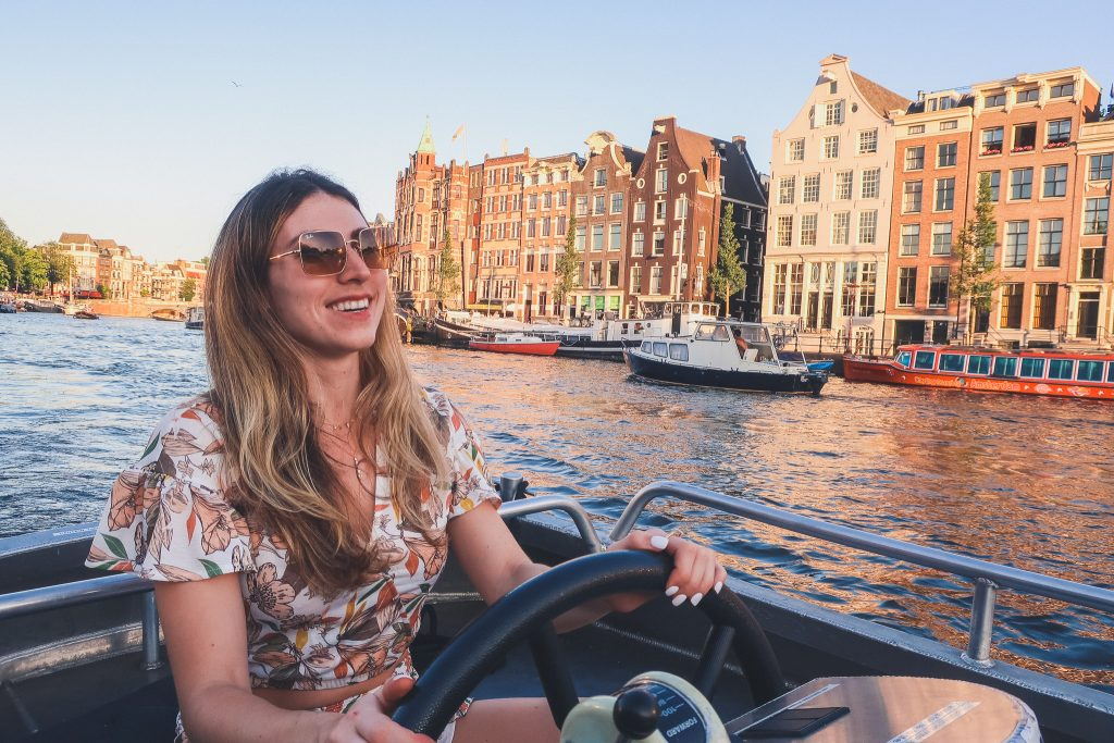Girl steering a boat on an Amsterdam Canal