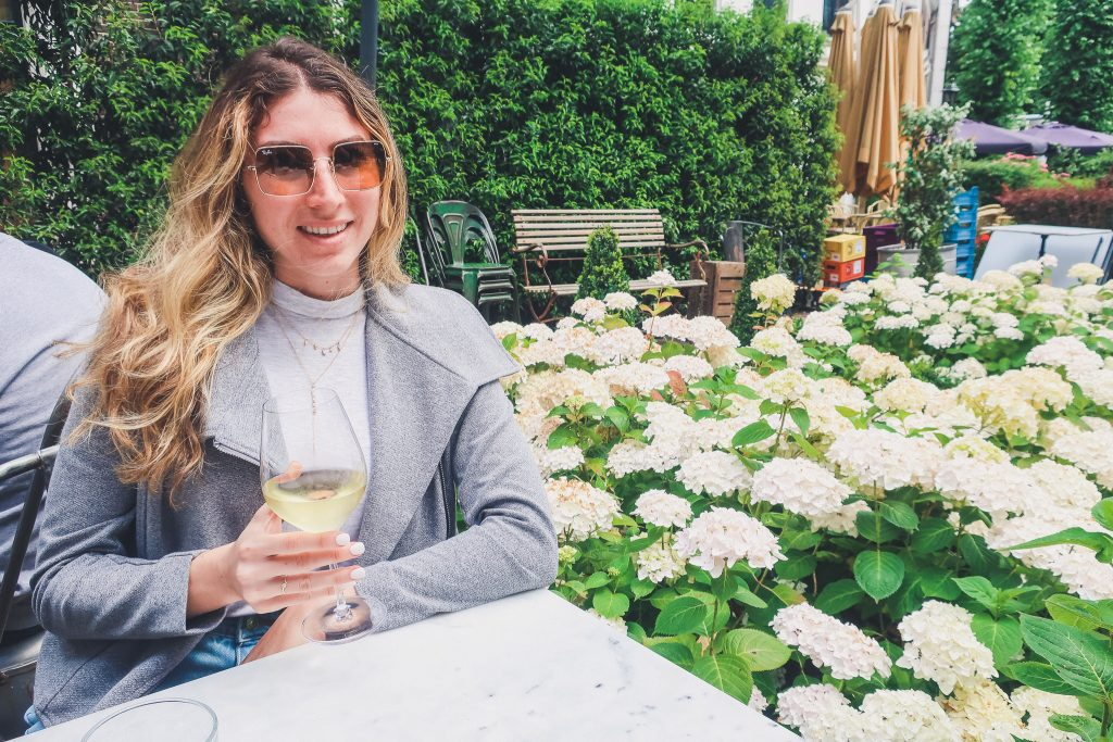 Girl holding glass of wine in the outdoor garden of Restaurant Lion Noir in Amsterdam