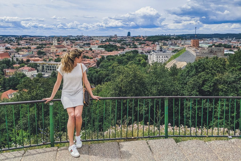Girl looks out from hill of 3 crosses at city of Vilnius