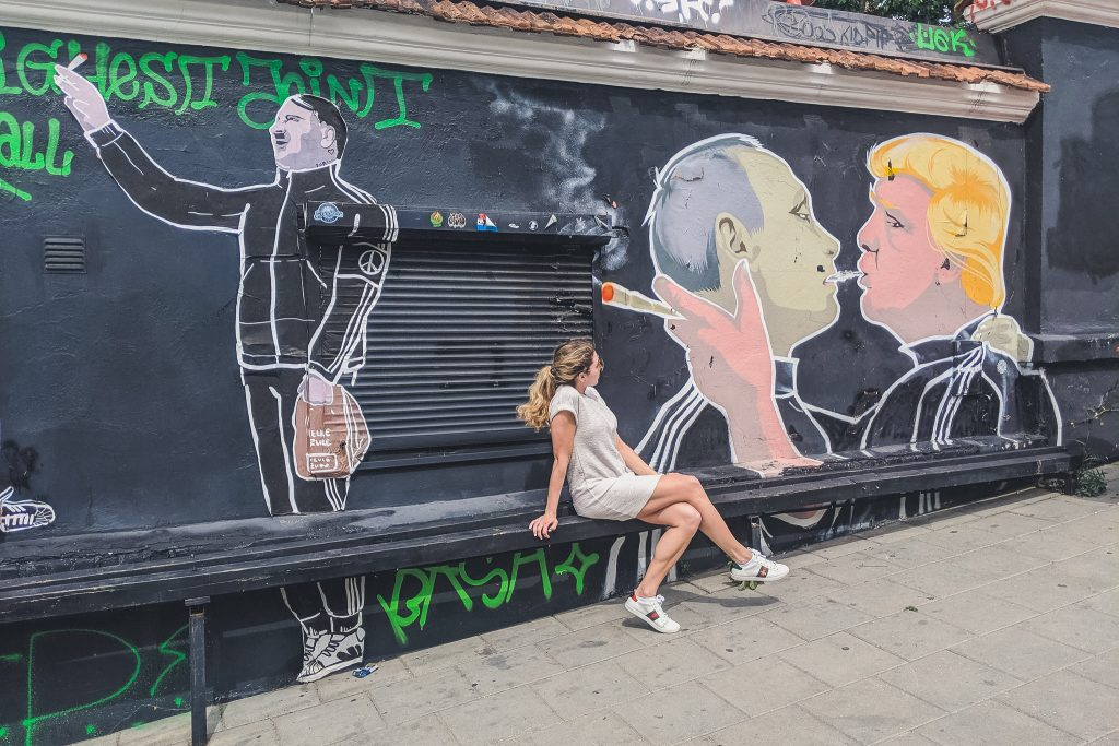 "Girl sits looking at ""Make Everything Great Again"" Mural in Vilnius"
