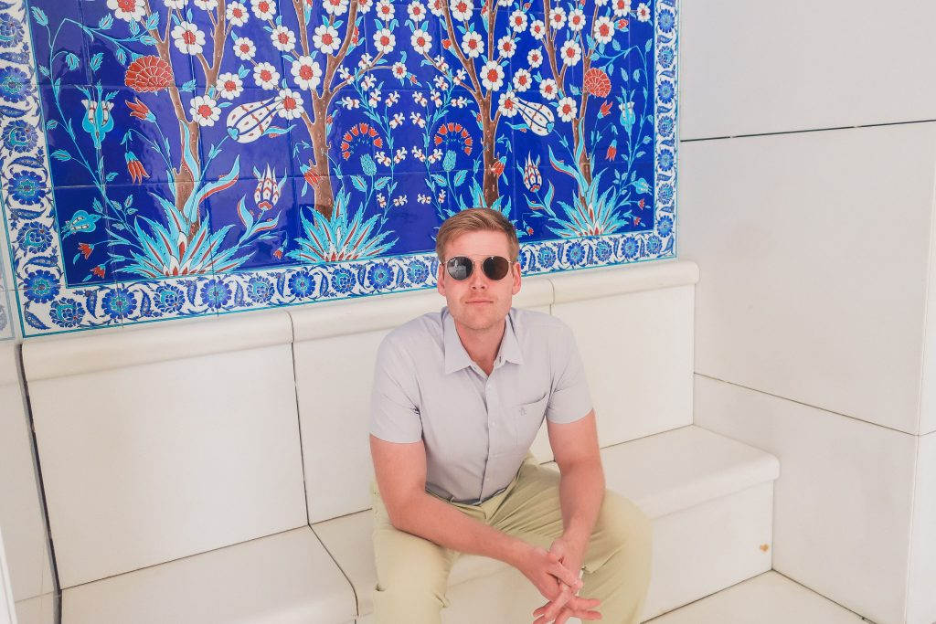 man sitting in front of beautiful tile design at Sheikh Zayed Grand Mosque