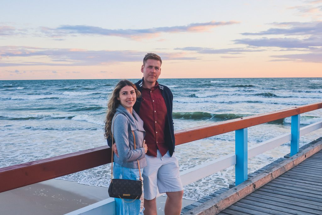 Couple standing on Palanga Pier at sunset