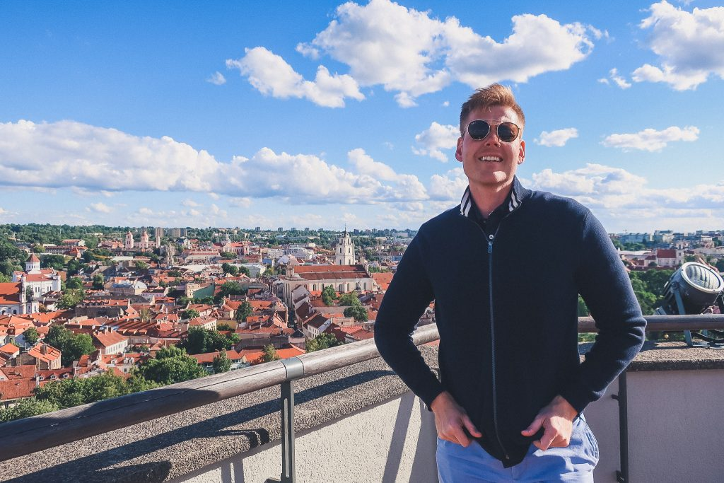 Man standing in front of Vilnius panorama at Gediminas Castle tower