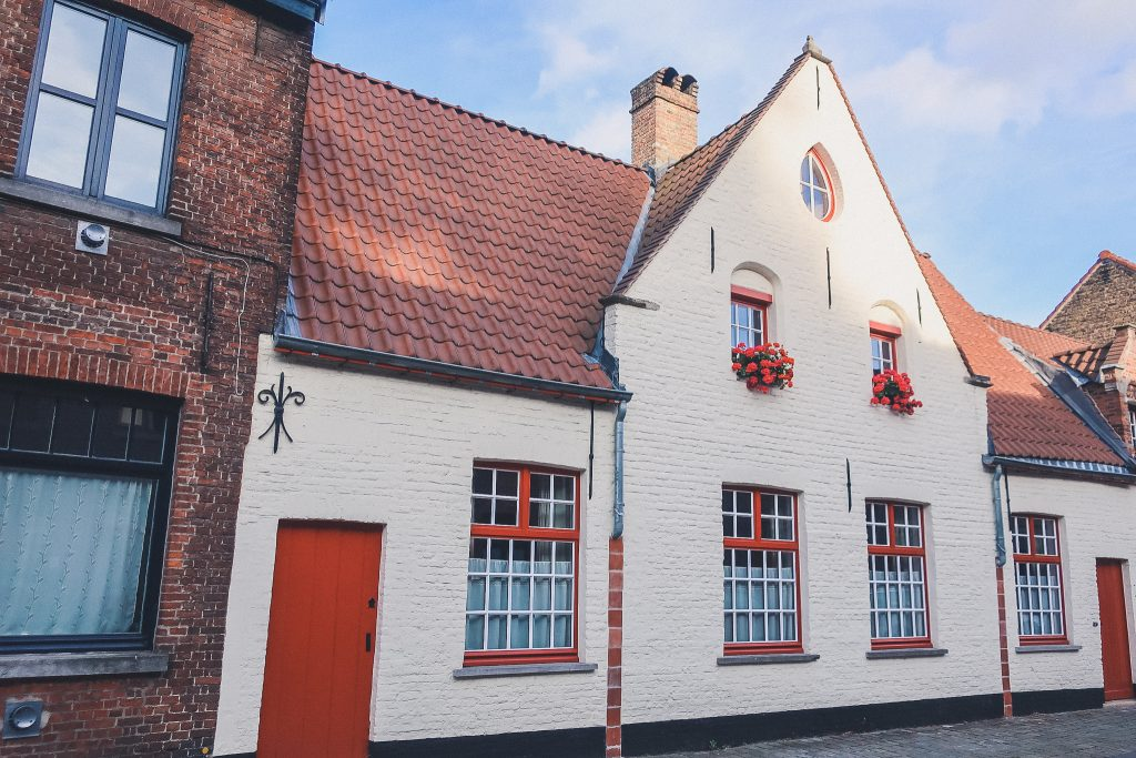 Home in Bruge with white paint and red door, red trim and red flowers