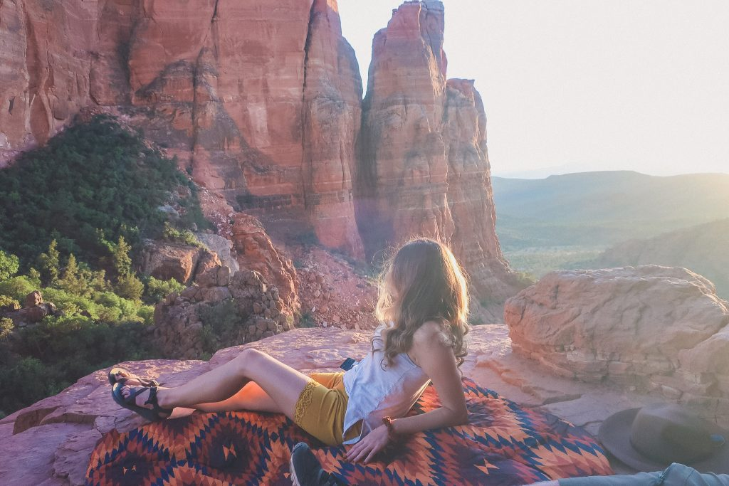 Girl watches the sunset at the top of Cathedral Rock in Sedona