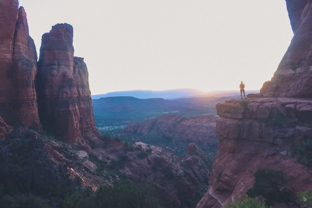 Girl watches sunset from Cathedral Rock in the distance