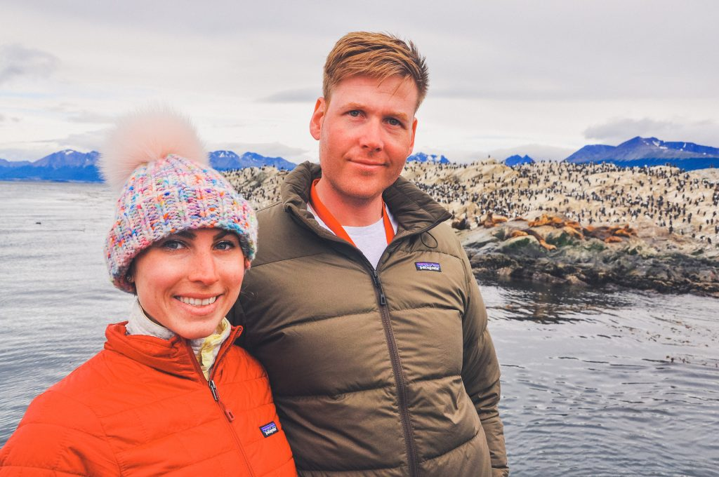 man and woman on a boat near Beagle Channel, woman wears fur pom hat