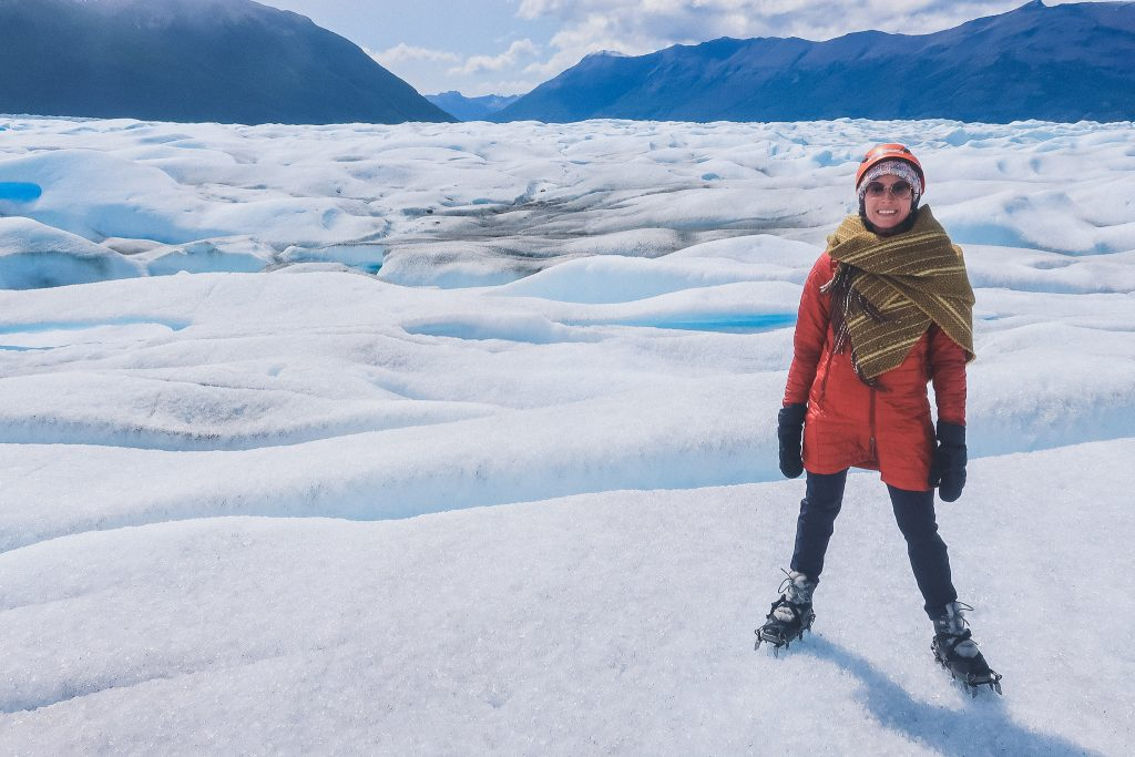 woman stands on glacier wearing compressible jacket and wool blanket scarf