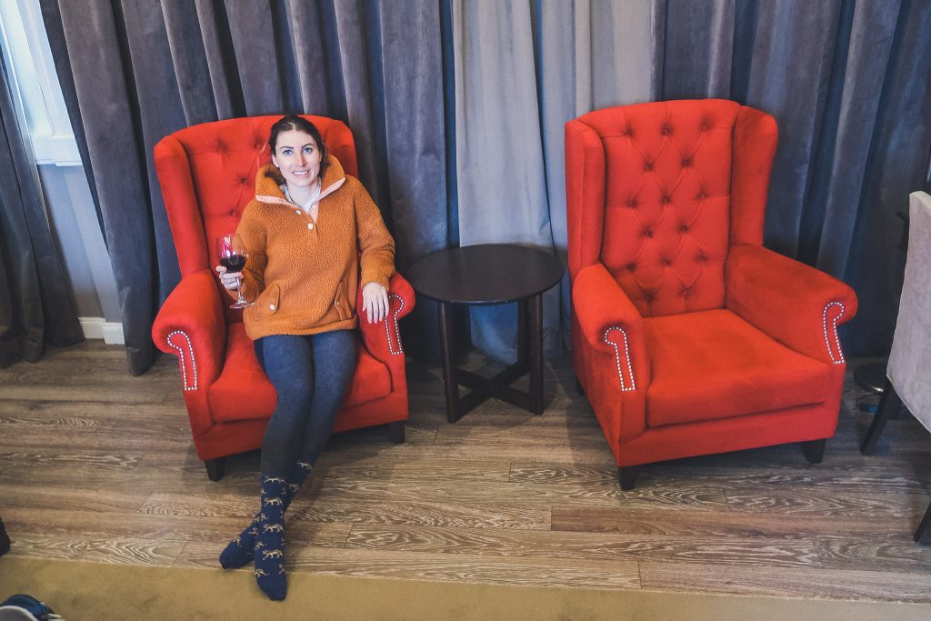 girl sits in big chair at hotel wearing fleece sweater