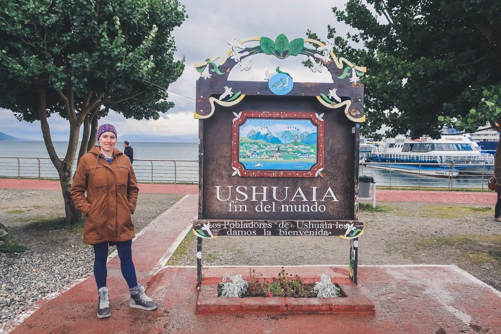 girl wearing furry snow boots stands in front of 'welcome to ushuaia sign'