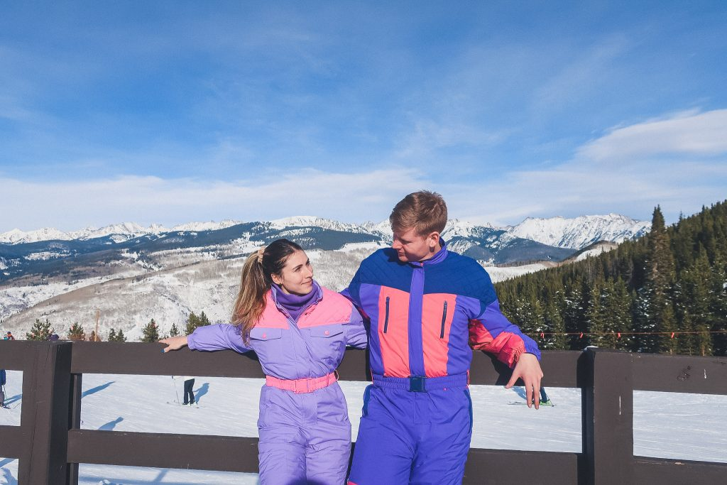 couple wears matching one piece snowsuits on mountain in Vail,CO