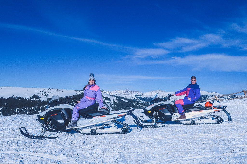 woman wears fur pom hat on snowmobile