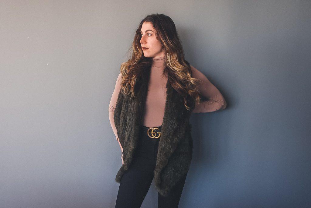 woman wears furry vest