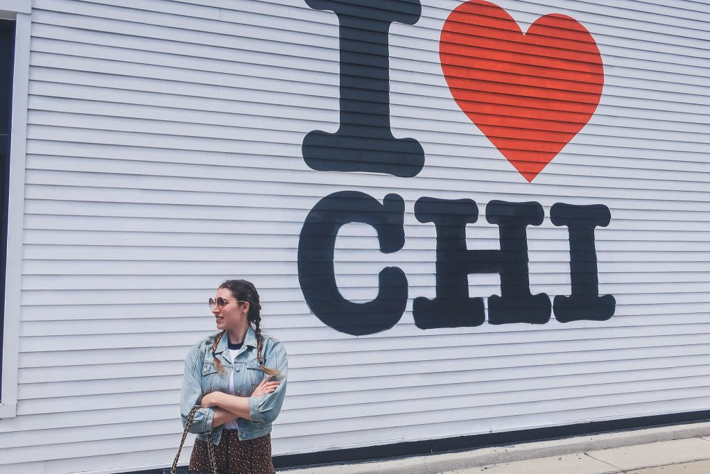 "woman stands in front of ""I love Chi"" mural"