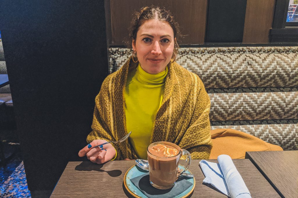 woman eats hot chocolate wearing long sleeve turtleneck and wool shawl