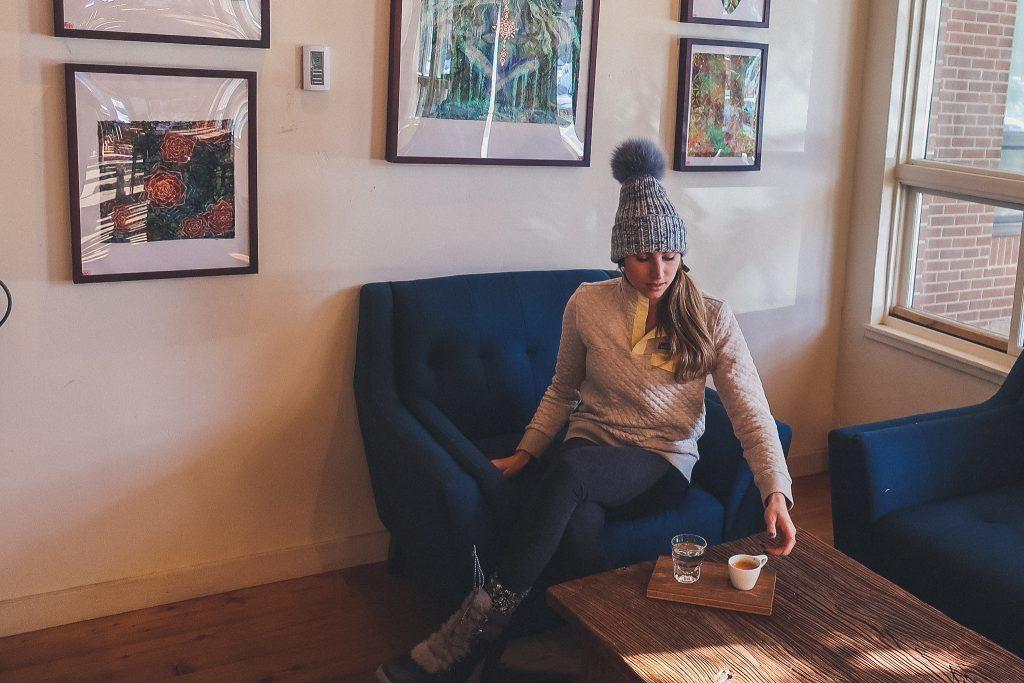 woman wears fur pom hoodie